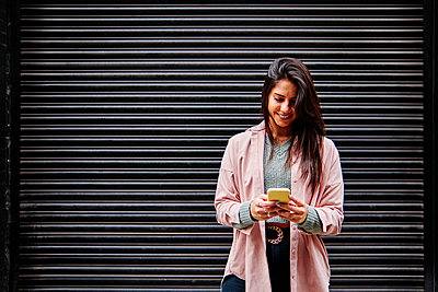 Smiling woman using mobile phone while standing in front of shutter - p300m2273666 by Angel Santana Garcia