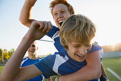 Three soccer players cheering on field. - p328m840835f by Hero Images