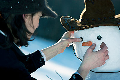 Mature woman placing the eyes on a snowman face - p429m911539f by WALTER ZERLA