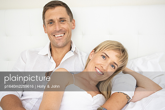 Happy couple sitting on bed, portrait - p1640m2259616 by Holly & John