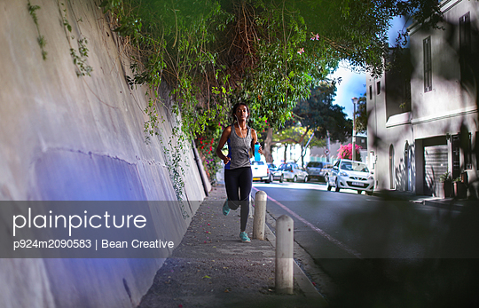 Young female runner running along city sidewalk - p924m2090583 by Bean Creative