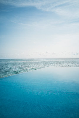 Tranquil blue infinity pool and ocean, Maldives, Indian Ocean - p1023m2024446 by Martin Barraud