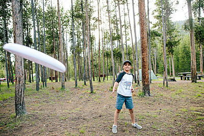 Boy throwing plastic disc while standing against trees in forest - p1166m2034965 by Cavan Images