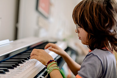 Side view of child playing on a smart piano keyword - p1166m2095843 by Cavan Images