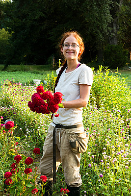 Young smiling woman holds freshly-cut red flowers in garden - p1166m2136442 by Cavan Images