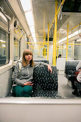 Junge Frau mit Rucksack sitzt in der U-Bahn  - p1212m1137019 von harry + lidy