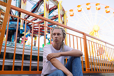 Portrait of teenager boy with dreadlocks sitting in amusement park - p1363m2007898 by Valery Skurydin