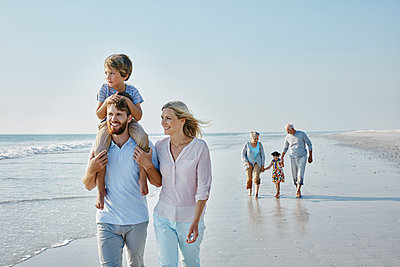 Happy extended family strolling on the beach - p300m1449445 by Roger Richter
