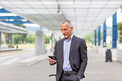 Male professional using smart phone at railroad station - p300m2287527 by Emma Innocenti