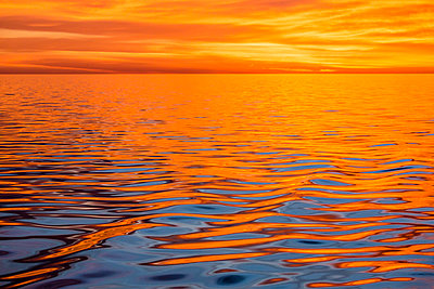 Beautiful sunset light reflected on a calm ocean near Isla San Marcos, Baja California Sur, Mexico, North America - p871m1561574 by Michael Nolan