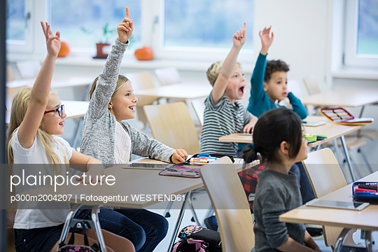 Happy pupils raising their hands in class - p300m2004207 by Fotoagentur WESTEND61