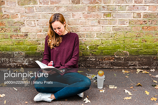 Woman reading book while sitting against brick wall on footpath - p300m2226511 by Manu Prats