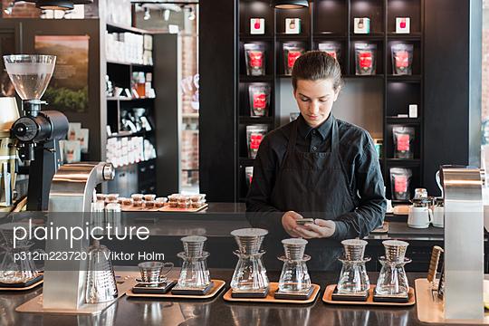 Female barista checking phone - p312m2237201 by Viktor Holm