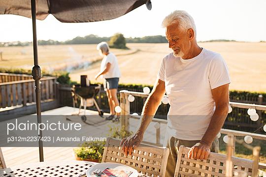 Man standing by table in garden - p312m2237423 by Amanda Falkman