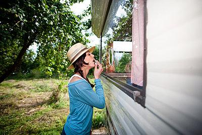 Junge Frau schminkt sich die Lippen am Wohnmobil - p1093m2193602 von Sven Hagolani