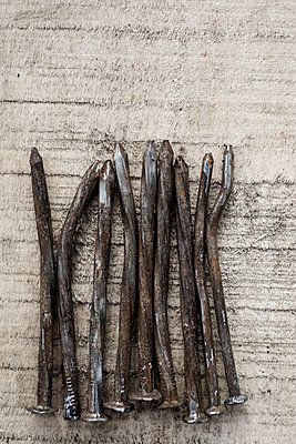 Nine bent, rusty old nails on rough sawn timber. - p1433m1574956 by Wolf Kettler