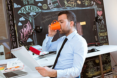 Businessman in creative office looking at documents and drinking coffee - p300m2012510 by Florian Küttler