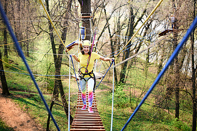 Young woman wearing yellow t-shirt and helmet in a rope course - p300m2102927 by Ekaterina Yakunina