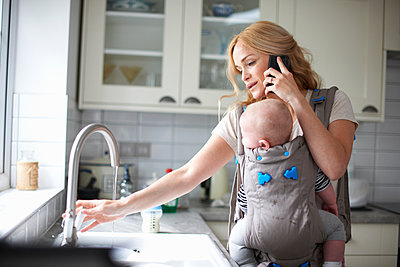 Woman holding baby boy in sling, using smartphone, turning on tap to do washing up - p429m1469564 by Peter Muller