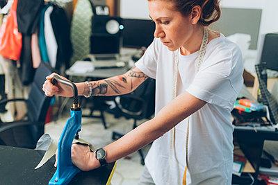 Fashion designer working in her studio - p429m2058382 by Eugenio Marongiu