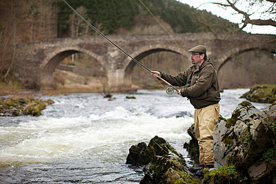 Man fishing for salmon in river - p429m659590f by Leon Harris
