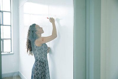 Mixed race businesswoman writing on whiteboard - p555m1504073 by John Fedele
