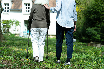 Carer and senior woman walking in garden - p623m2165453 by Frederic Cirou