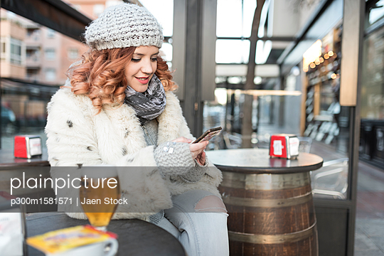 Young woman using cell phone on terrace of a pub in winter - p300m1581571 von Jaen Stock