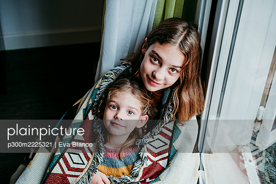 Sisters covered in blanket sitting by window at home - p300m2225321 by Eva Blanco