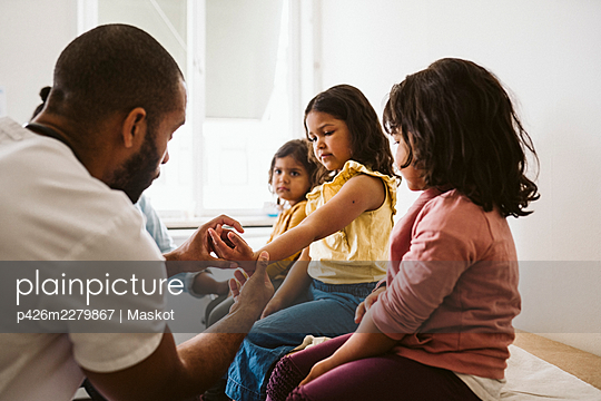 Male healthcare worker examining girl's hand sitting by sisters at medical clinic - p426m2279867 by Maskot