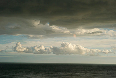 Clouds in sky with a stormy sea - p1072m829552 by Tracy Jean Shields