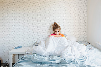 Young girl sitting in messy bed looking at her digital device - p1166m2189797 by Cavan Images