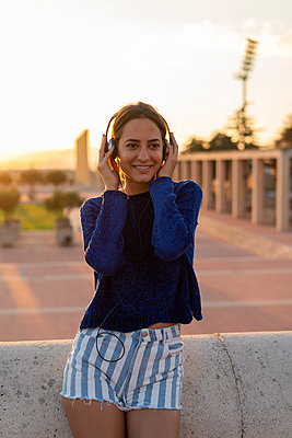 Spain, Barcelona, Montjuic, smiling young woman listening to music with headphones at sunset - p300m2058593 by VITTA GALLERY