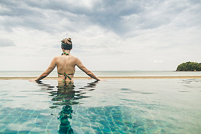 Rear view of woman in infinity pool, Koh Lanta, Thailand - p300m2166458 by Christophe Papke