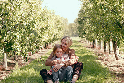 Happy mother with daughter sitting on grass in orchard - p300m2275632 by Katharina Mikhrin
