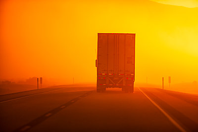 Truck driving down road in dust storm - p555m1479566 by Eric Raptosh Photography