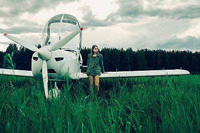 Caucasian woman leaning on airplane wing - p555m1522966 by Vladimir Serov