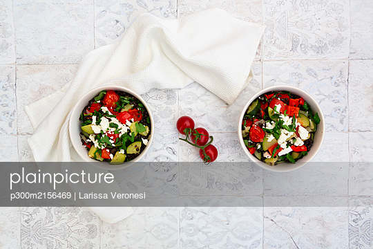 Bowls of salad with beluga lentils, tomatoes, paprika, zucchini, feta cheese, mint and parsley - p300m2156469 by Larissa Veronesi