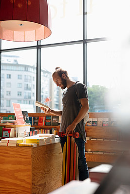 Man with skateboard shopping in bookstore - p1192m2016945 by Hero Images