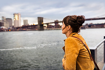 Side view of woman looking at East River while standing against Brooklyn bridge - p1264m1172996 by Astrakan