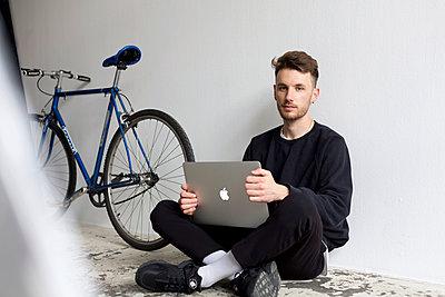 Junger Mann mit Laptop Computer sitzt auf dem Fußboden - p1301m1582604 von Delia Baum