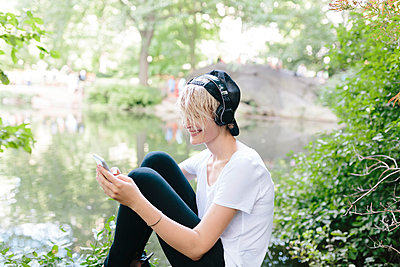 Young woman sitting at lakeside in park wearing headphones and looking at cell phone - p300m1356256 by Boy photography