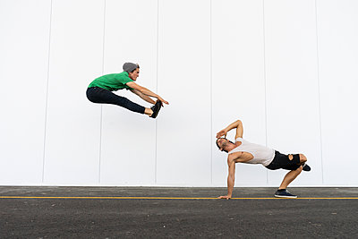 Two acrobats doing tricks together, jumping mid-air - p300m2012360 von VITTA GALLERY