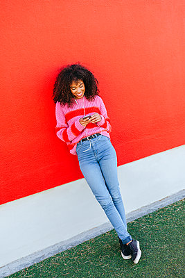 Smiling young woman with earphones leaning against red wall looking at cell phone - p300m2059099 von Kiko Jimenez