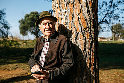 Spain, Barcelona. Senior man retired in a park with his hat resting on a tree and using the phone - p300m2166549 von Josep Rovirosa