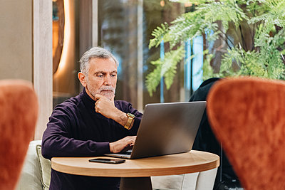 Thoughtful mature businessman using laptop while sitting with hand on chin in hotel - p300m2273790 by Daniel González