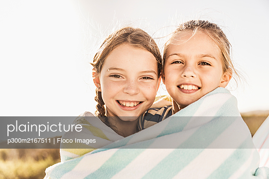 Portrait of two happy cute girls wrapped in a towel - p300m2167511 by Floco Images