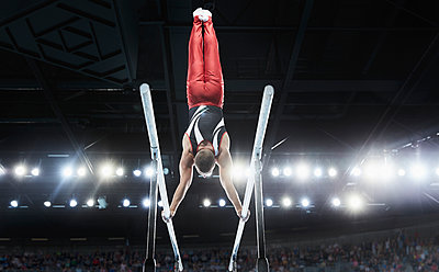 Male gymnast performing upside-down handstand on parallel bars in arena - p1023m1217745 by Chris Ryan