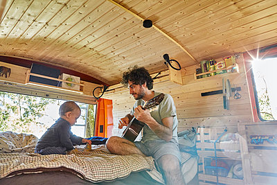 Father playing guitar, baby boy listens in mobile home - p1146m2196044 by Stephanie Uhlenbrock