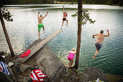 Mature couples jumping off diving board and rocks into lake - p1192m2017166 by Hero Images